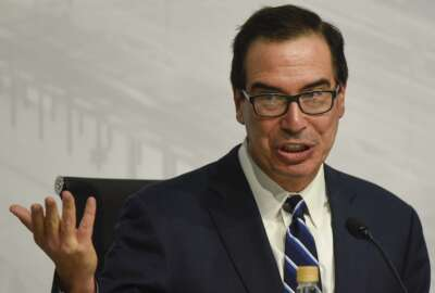 ILE - In this July 22, 2018 file photo, U.S. Treasury Secretary Steven Mnuchin speaks during a news conference at the G20 meeting of Finance Ministers and Central Bank governors in Buenos Aires, Argentina.  The Treasury Department has issued new rules on foreign investments into American companies that will give the government more power to block foreign transactions on national security grounds. The rules represent the latest escalation in an intensifying economic conflict between the United States and China. (AP Photo/Gustavo Garello)