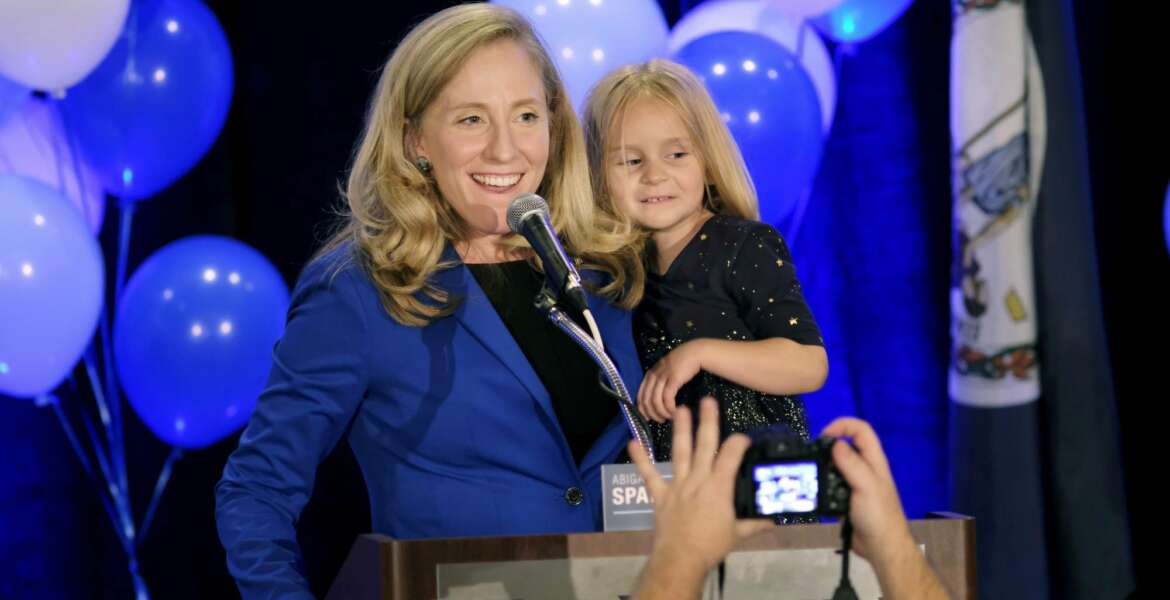Democrat Abigail Spanberger claims victory in the 7th district Virginia congressional race while holding her daughter Catherine, 4, during a victory party in Richmond, Va., late Tuesday, Nov. 6, 2018. She defeated two-term Republican congressman Dave Brat. (Dean Hoffmeyer/Richmond Times-Dispatch via AP)