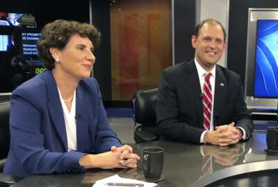 In this Oct. 29, 2018 photo, Kentucky's 6th Congressional District candidates Amy McGrath, left, Andy Barr, center, pose for photos before the start of a debate in Lexington, Ky.  Barr, the Republican incumbent, faces a tough challenge from McGrath, a Democrat. The Lexington-area battle pits third-term Republican Rep. Andy Barr against Democrat Amy McGrath, a retired Marine fighter pilot. Trump won the 6th District by more than 15 percentage points in 2016. But with the help of carefully-shaped campaign ads that went viral, McGrath holds the edge on campaign fundraising.  (AP Photo/Adam Beam)