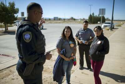 In this Nov. 15, 2018 photo provided by Ivan Pierre Aguirre, Dalila Reynoso-Gonzalez, center left, a program director for the Methodist immigration advocacy group Justice for our Neighbors of East Texas, and another protestor talk with a Department of Homeland Security official outside the Tornillo detention camp holding more than 2,300 migrant teens in Tornillo, Texas. The Trump administration announced in June 2018 that it would open the temporary shelter for up to 360 migrant children in this isolated corner of the Texas desert. Less than six months later, the facility has expanded into a detention camp holding thousands of teenagers - and it shows every sign of becoming more permanent. (Ivan Pierre Aguirre via AP)