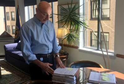 In this Aug. 7, 2018, photo, Mark Robbins, the last remaining member of the Merit Systems Protection Board, looks through stacks of legal cases piled up on his desk in Washington office. Robbins reads through federal workplace disputes, analyzes the cases, marks them with notes and logs his legal opinions. He then passes them along to nobody. He's the only member of a three-member board that legally can't operate until the president and Congress give him at least one colleague. (AP Photo/Juliet Linderman)