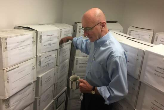 In this Aug. 7, 2018, photo, Mark Robbins, the sole member of the Merit Systems Protection Board, walks through the supply closet, pointing to boxes full of cases, in his office in Washington. Robbins reads through federal workplace disputes, analyzes the cases, marks them with notes and logs his legal opinions. He then passes them along to nobody. He's the only member of a three-member board that legally can't operate until the president and Congress give him at least one colleague.  (AP Photo/Juliet Linderman)
