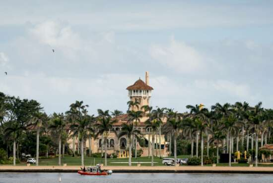 """FILE - In this Feb. 19, 2018, file photo, Mar-a-Lago is visible from a motorcade carrying President Donald Trump, in Palm Beach, Fla. Trump is making his return to Florida, kicking off the Palm Beach social season at his """"winter White House."""" All presidents have had their favorite refuges from Washington. But none has drawn the fascination or raised the ethical issues of Mar-a-Lago, where Trump spends his days mixing work, business and play in the company of dues-paying members and staff are on high alert for those seeking influence.(AP Photo/Andrew Harnik, File)"""