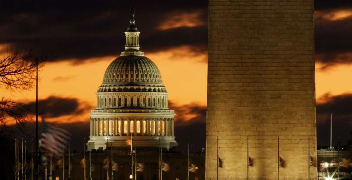 The U.S. Capitol dome is seen past the base of the Washington Monument just before sunrise in Washington, Saturday, Dec. 22, 2018. Hundreds of thousands of federal workers faced a partial government shutdown early Saturday after Democrats refused to meet President Donald Trump's demands for $5 billion to start erecting a border wall with Mexico. Overall, more than 800,000 federal employees would see their jobs disrupted, including more than half who would be forced to continue working without pay. (AP Photo/Carolyn Kaster)