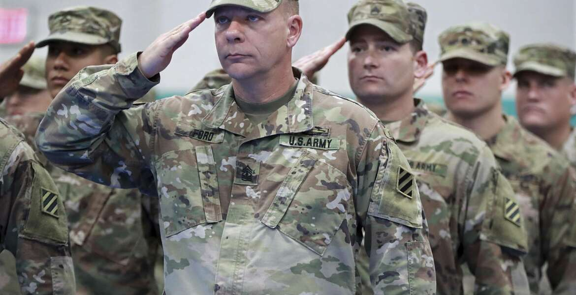 First sergeant Archer Ford, from left, sergeant first class Andreson Neal, and members of the Georgia National Guard's 48th Brigade Combat Team salute the colors during the Casing of Color and Departure Ceremony for their deployment to Afghanistan on Friday, Dec 21, 2018, at Fort Stewart. (Curtis Compton/Atlanta Journal-Constitution via AP)