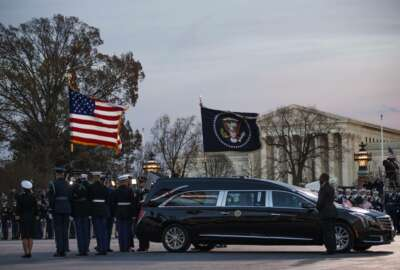 A joint services military honor guard removes the casket of former President George H.W. Bush from the hearse to carry it into the rotunda of the U.S. Capitol in Washington to lie in state, Monday, Dec. 3, 2018. (Shawn Thew/Pool Photo via AP)