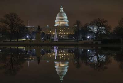 The Capitol is mirrored in the Reflecting Pool in Washington, as a partial government shutdown heads into a second week, Friday night, Dec. 28, 2018. Both chambers of Congress are gone, likely leaving the impasse till next week when the Democrats take control of the House of Representatives. (AP Photo/J. Scott Applewhite)