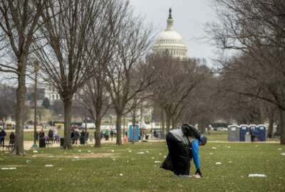 The Capitol building is visible as a man who declined to give his name picks up garbage during a partial government shutdown on the National Mall in Washington, Tuesday, Dec. 25, 2018. (AP Photo/Andrew Harnik)