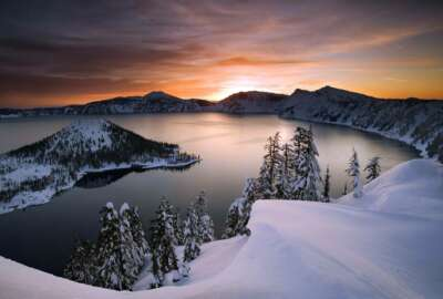 FILE - In this January 2006 file photo, the sun rises over Crater Lake, Ore. Access to Crater Lake and other national parks will be limited due to the government shutdown. (Marc Adamus/The Register-Guard via AP, File)