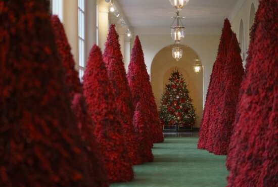 FILE - In this Nov. 26, 2018, file photo, topiary trees line the East colonnade during the 2018 Christmas preview at the White House in Washington. Melania Trump's cranberry topiary trees may have left some of her critics seeing red, but they turned out to be a hit this Christmas _ one of several new wrinkles the Trumps introduced this holiday season. (AP Photo/Carolyn Kaster, File)