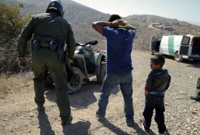 FILE - In this June 28, 2018, file photo, a Guatemalan father and son, who crossed the U.S.-Mexico border illegally, are apprehended by a U.S. Border Patrol agent in San Diego. Children torn from their parents, refugees turned away, tear gas fired on asylum-seekers, and a swath of the globe derided by the president in crude language. In a breathless 2018, they were just a handful of headlines on immigration, one of the year's most dominant issues. (AP Photo/Jae C. Hong, File)