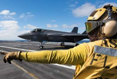 """Aviation Boatswain's Mate (Handling) 3rd Class Christian Cottman directs an F-35C Lightning II assigned to the """"Argonauts"""" of Strike Fighter Squadron (VFA) 147 on the flight deck of Nimitz-class aircraft carrier USS Carl Vinson"""