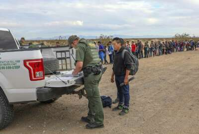 This Monday, Jan. 14, 2019 photo released by U.S. Customs and Border Protection shows some of 376 Central Americans the Border Patrol says it arrested in southwest Arizona, the vast majority of them families, who used short holes dug under a barrier to cross the border in multiple spots about 10 miles east of San Luis, Ariz. The unusually large group was almost entirely from Guatemala. (U.S. Customs and Border Protection via AP)