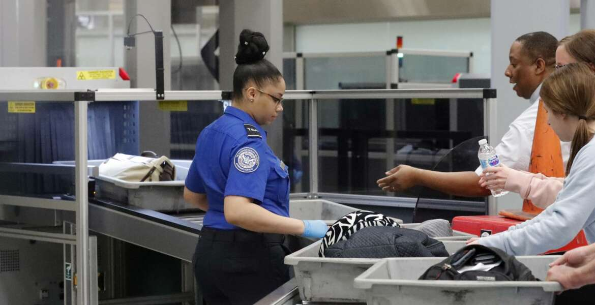 A Transportation Security Administration employee helps air travelers submit their bags for inspection at Hartsfield Jackson Atlanta International Airport Monday, Jan. 7, 2019, in Atlanta. (AP Photo/John Bazemore)