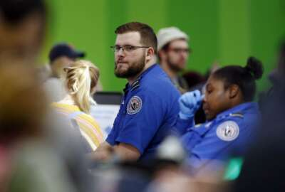 Transportation Security Administration officers work at a checkpoint at Logan International Airport in Boston, Saturday, Jan. 5, 2019. The TSA acknowledged an increase in the number of its employees calling off work during the partial government shutdown. (AP Photo/Michael Dwyer)
