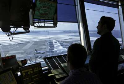 FILE - In this March 16, 2017, file photo, air traffic controllers work in the tower at John F. Kennedy International Airport in New York. The partial government shutdown is starting to effect air travelers. Over the weekend, some airports had long lines at checkpoints, apparently caused by a rising number of security officers calling in sick while they are not getting paid. (AP Photo/Seth Wenig, File)