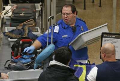 A TSA worker helps passengers at the Salt Lake City International Airport Wednesday Jan., 16, 2019, in Salt Lake City. The government shutdown has generated an outpouring of generosity to TSA agents and other federal employees who are working without pay. In Salt Lake City, airport officials treated workers from the TSA, FAA and Customs and Border Protection to a free barbecue lunch as a gesture to keep their spirits up during a difficult time. (AP Photo/Rick Bowmer)