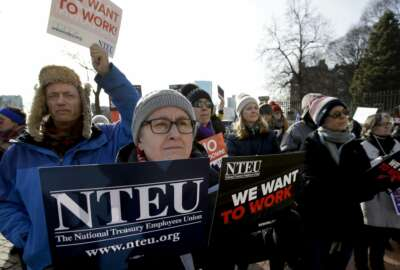 United States Department of Agriculture employee Lori Lodato, of Wilmington, Mass., display placards during a rally by federal employees and supporters, Thursday, Jan. 17, 2019, in front of the Statehouse in Boston, held to call for an end of the partial shutdown of the federal government. (AP Photo/Steven Senne)
