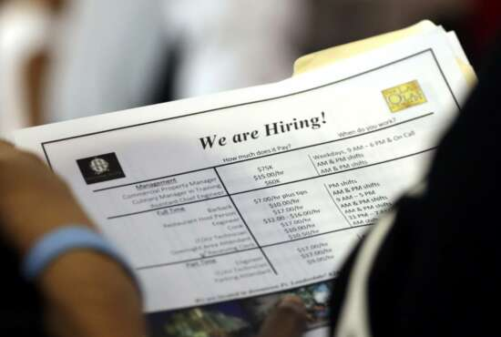 FILE-In this June 21, 2018 file photo, a job applicant looks at job listings for the Riverside Hotel at a job fair hosted by Job News South Florida, in Sunrise, Fla.  The Labor Department is expected to issue its new regulations on overtime in 2019, which employees must be given overtime, and which are exempt. (AP Photo/Lynne Sladky)