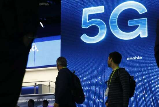 """FILE- In this Jan. 9, 2019, file photo a sign advertises 5G at the Qualcomm booth at CES International in Las Vegas. 5G is a new technical standard for wireless networks that promises faster speeds; less lag, or """"latency,"""" when connecting to the network; and the ability to connect many devices to the internet without bogging it down. (AP Photo/John Locher, File)"""