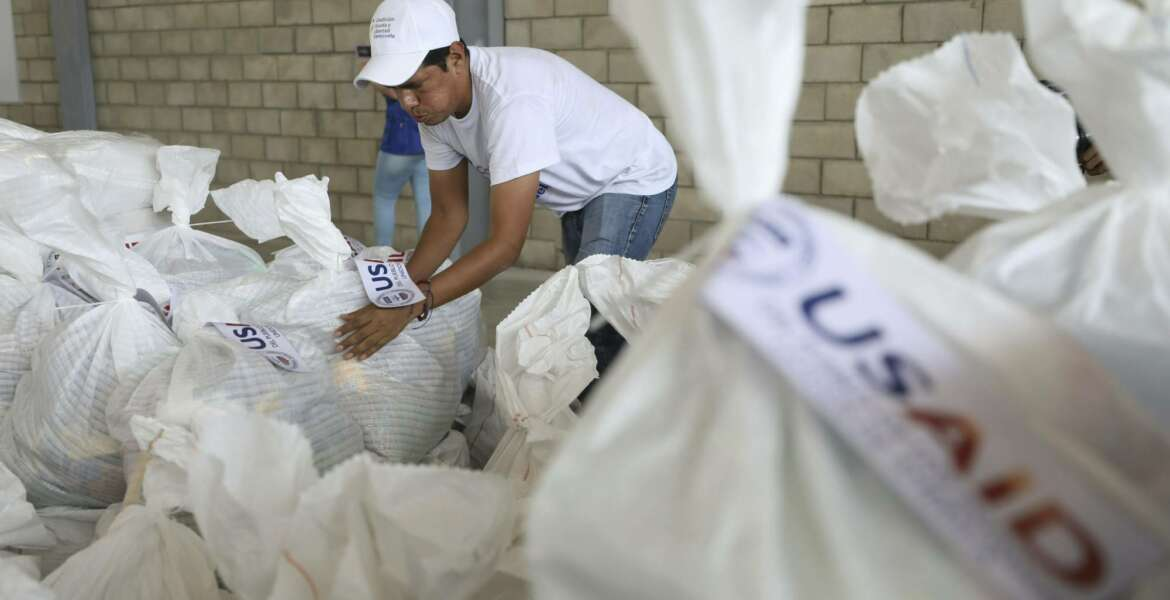 A Venezuelan volunteer places a bag of USAID humanitarian aid for storage at a warehouse next to the Tienditas International Bridge, near Cucuta, Colombia, on the border with Venezuela, Friday, Feb. 8, 2019. Trucks carrying U.S. humanitarian aid destined for Venezuela arrived Thursday at the Colombian border, where opposition leaders vowed to bring them into their troubled nation despite objections from embattled President Nicolas Maduro. (AP Photo/Fernando Vergara)