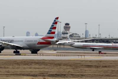 Jets line up on the tarmac at Dallas/Fort Worth International Airport in Grapevine, Dallas, Wednesday, Feb. 13, 2019. Flights at Dallas' two major airports were temporarily halted after air traffic controllers were forced to evacuate a building because of smoke, and the resulting flight delays are expected to continue for hours. (AP Photo/LM Otero)