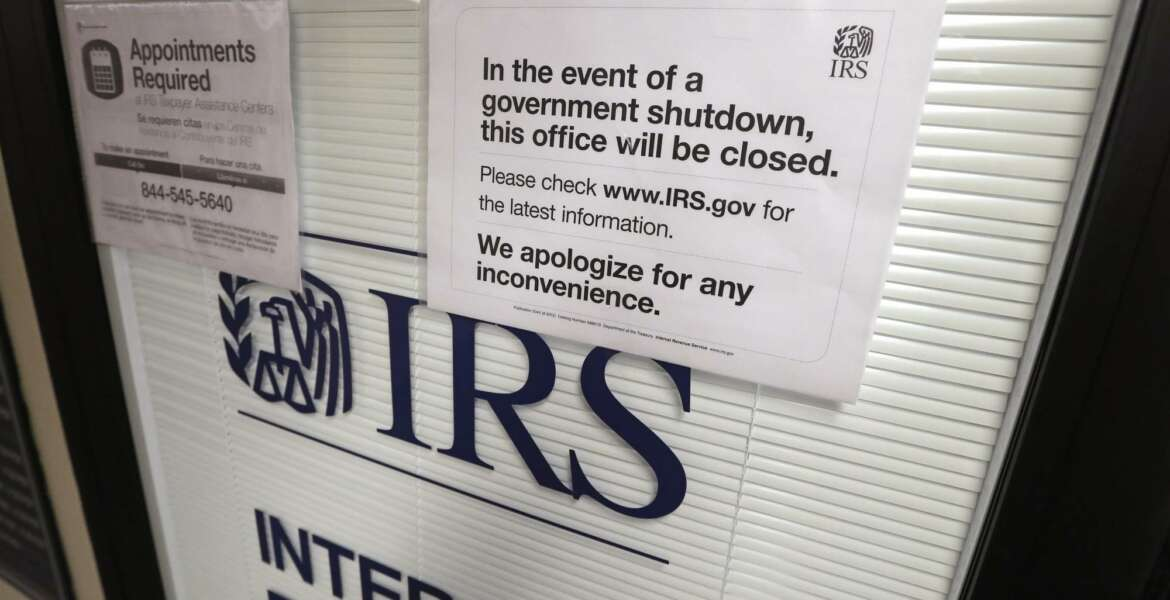 """FILE- In this Jan. 16, 2019, file photo doors at the Internal Revenue Service (IRS) in the Henry M. Jackson Federal Building are locked and covered with blinds as a sign posted advises that the office will be closed during the partial government shutdown in Seattle. Disruptions from last month's partial government shutdown caused a """"shocking"""" deterioration in the IRS' telephone help for taxpayers in the first week of the filing season, the agency's watchdog said in a report released Tuesday, Feb. 12. (AP Photo/Elaine Thompson, File)"""