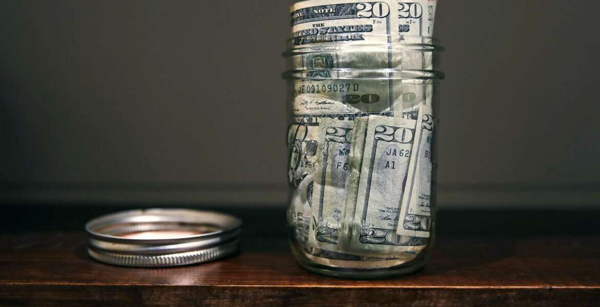 FILE - In this June 15, 2018, file photo a canning jar filled with currency sits on a shelf in East Derry, N.H. An emergency fund doesn't have to be wishful thinking when you're building your financial life. Start small to build a habit, use windfalls to kick-start your fund and have a plan for irregular expenses. (AP Photo/Charles Krupa, File)