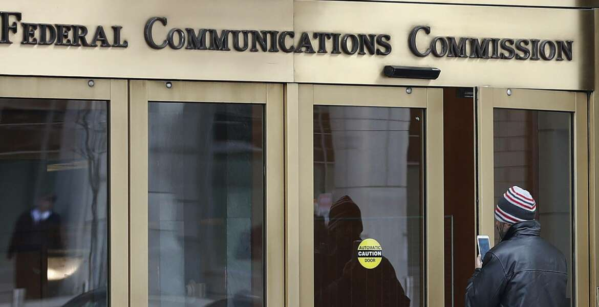 FILE - In this Thursday, Dec. 14, 2017, file photo, a person with a smartphone enters the Federal Communications Commission building in Washington. Tech companies and nearly two dozen U.S. states clashed with the government in federal court Friday, Feb. 1, 2019, over the repeal of net neutrality, a set of Obama-era rules aimed at preventing big internet providers from discriminating against certain technology and services. The action rolling back the neutrality rules
