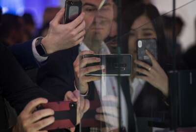 Attendees take pictures of the new Huawei Mate X foldable 5G smartphone during the Mobile World Congress wireless show, in Barcelona, Spain, Monday, Feb. 25, 2019. The annual Mobile World Congress (MWC) runs from 25-28 February in Barcelona, where companies from all over the world gather to share new products. (AP Photo/Emilio Morenatti)