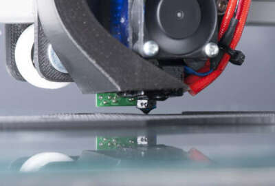 Photo of a 3D printer actually in action printing a part. You can see the fan moving and the part it is printing.