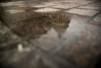FILE- In this Feb. 22, 2019, file photo the dome of the U.S. Capitol Building is visible in reflection in Washington. On Friday, March 22, the Treasury Department releases federal budget data for February. (AP Photo/Andrew Harnik, File)
