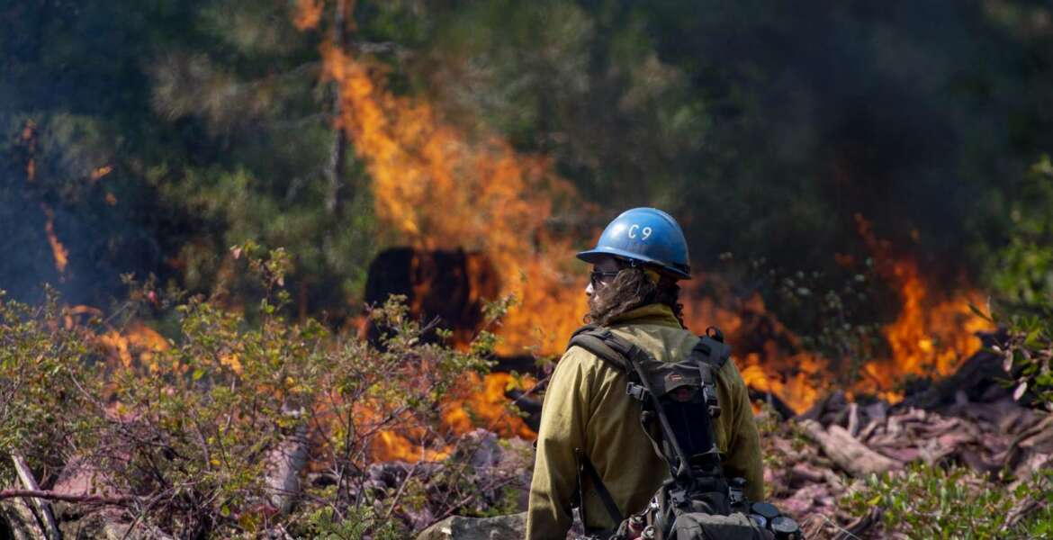 In this Sept. 4, 2018, photo, Tyler Medders of the Susanville Hot Shots keeps an eye out for embers at the North Fire near the North Fork Campgrounds in Placer County in Emigrant Gap, Calif. With nearly 40 million people living in California and development spreading into once-wild regions, some of the state's best tools toward preventing wildfires can't be widely used. Still, there is growing agreement that the state must step up its use of forest management through prescribed burns and vegetation removal in an attempt to lessen the impact of wildfires. (Jose Villegas/Sacramento Bee via AP)