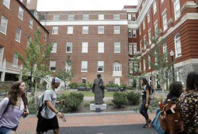 FILE - In this Sept. 1, 2016 file photo, students walk past a Jesuit statue in front of Isaac Hawkins Hall, center, formerly named Mulledy Hall, on the Georgetown University campus, in Washington. Georgetown University undergraduates have voted Thursday, April 11, 2019, in favor of a referendum seeking the establishment of a fund benefiting the descendants of enslaved people sold to pay off the school's debts. (AP Photo/Jacquelyn Martin, File)