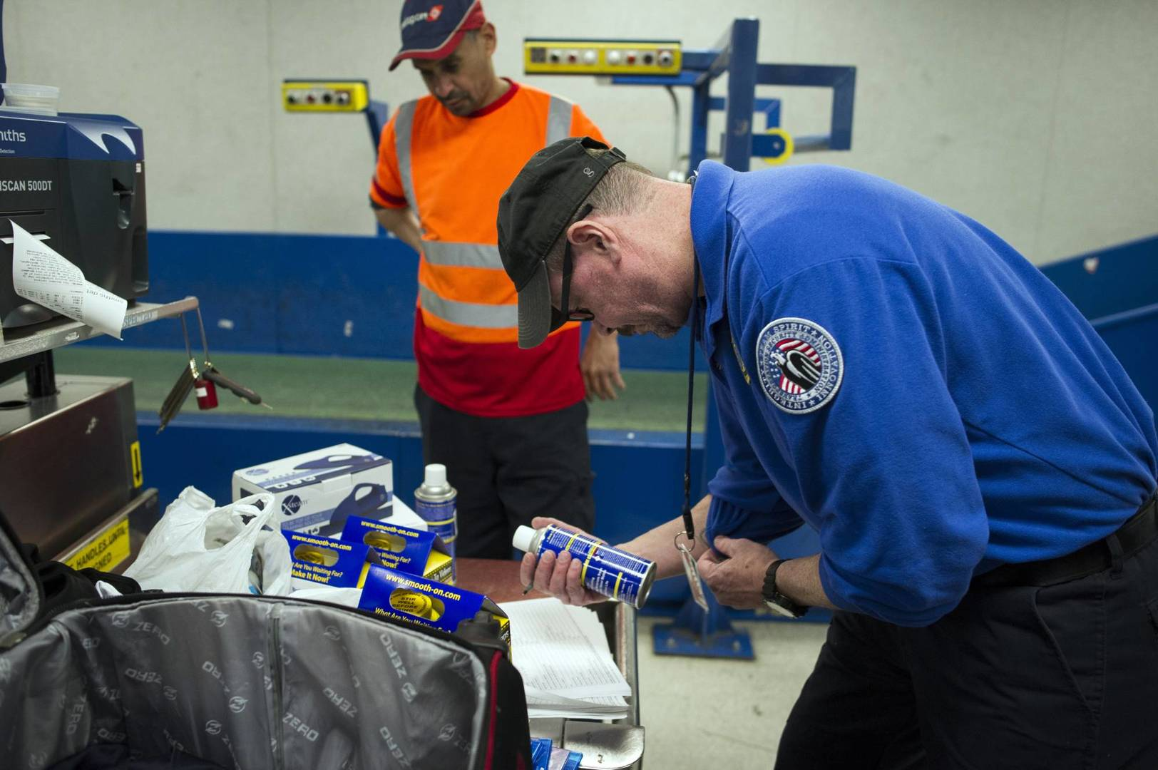 A Transportation Security Adminstration (TSA) transport security officer inspects a can which was packed in a suitcase flagged for a seconday inspection at Dulles International Airport in Dulles, Va., Tuesday, March 26, 2019. The can and the suitcase it was packed in was flagged for a secondary inspection at the intial TSA checkpoint the passenger passed through. TSA's social media presence has been something of a model for other federal agencies _ striking a tone is humorous, but still gives travelers informational dos and don'ts. (AP Photo/Cliff Owen)