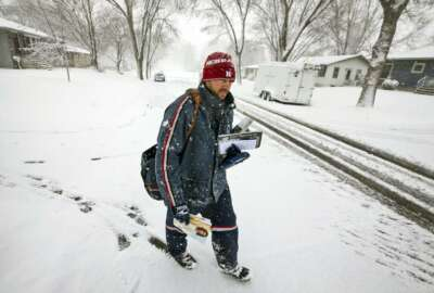 United States Postal Service city carrier Chad Jacobs delivers mail along 16th Avenue Northwest as snow falls, Wednesday, April 10, 2019, in Rochester, Minn. Jacobs said he doesn't mind cold and prefers it over hot days. (Andrew Link/The Rochester Post-Bulletin via AP)