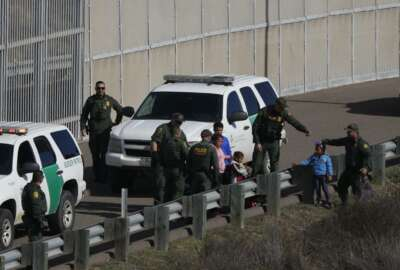 FILE - In this Dec. 9, 2018 file photo, a woman and children are ushered into cars by U.S. Border Patrol agents after crossing illegally over the border wall into San Diego, Calif., as seen from Tijuana, Mexico. A federal judge in California on Friday, May 17, 2019, will consider a challenge to President Donald Trump's plan to tap billions of dollars from the Defense and Treasury departments to build his prized border wall with Mexico. (AP Photo/Rebecca Blackwell, File)
