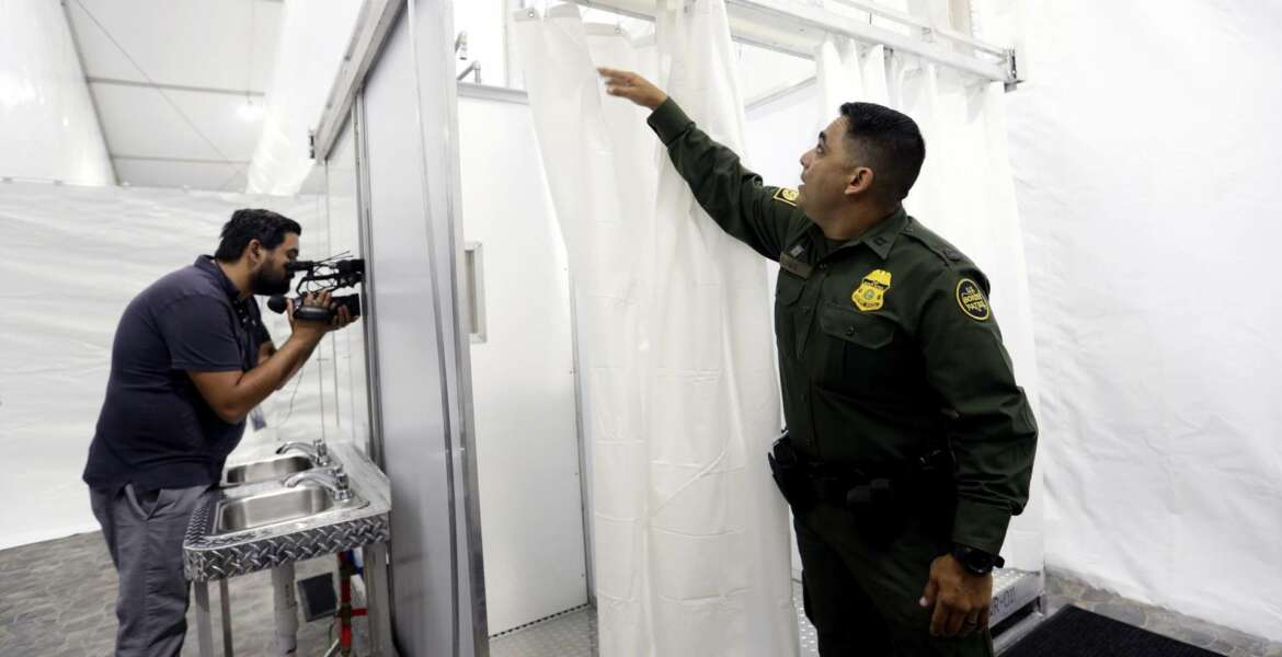 Border Patrol agent E. Flores shows the shower section during a media tour of a new U.S. Customs and Border Protection temporary facility near the Donna International Bridge, Thursday, May 2, 2019, in Donna, Texas. Officials say the site will primarily be used as a temporary site for processing and care of unaccompanied migrant children and families and will increase the Border Patrol's capacity to process migrant families. (AP Photo/Eric Gay)