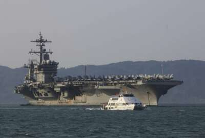 FILE - In this March 5, 2018, file photo, a Vietnamese passenger boat sails past U.S. aircraft carrier USS Carl Vinson as it docks in Danang bay, Vietnam. A U.S. sailor has pleaded guilty to espionage and sentenced to three years after admitting he took classified information about a Navy's nuclear-powered warship and planned to give it to a journalist and then defect to Russia officials said Friday, May 24, 2019. Jeff Houston of the Naval Criminal Investigative Service or NCIS said that U.S. Navy Petty Officer 2nd Class Stephen Kellogg III wished to publish an expose on waste within the military and admitted he wanted to share the information with Russians. Kellogg, who joined the Navy in 2014 served aboard the USS Carl Vinson from 2016 to 2018. (AP Photo/Hau Dinh, File)