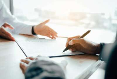 Client signing a real estate contract on desk in office.