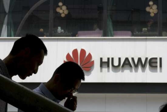 In this May 16, 2019, photo, Chinese men pass by a Huawei retail shop in Beijing. Stepping up the pressure on Beijing, the U.S. Commerce Department has effectively barred U.S. companies from selling or transferring technology to Huawei Technologies, the world's biggest maker of network gear, No. 2 smartphone manufacturer and a champion of Chinese industry. (AP Photo/Ng Han Guan)