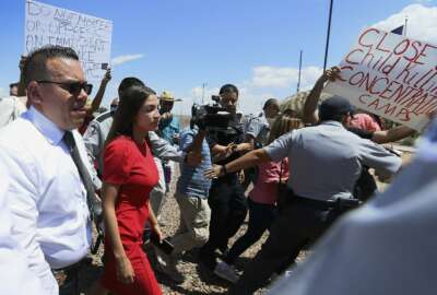 U.S. Rep. Alexandria Ocasio-Cortez, D-New York, is escorted back to her vehicle after she speaks at the Border Patrol station in Clint, Texas, about what she saw at area border facilities Monday, July 1, 2019. (Briana Sanchez/El Paso Times via AP)