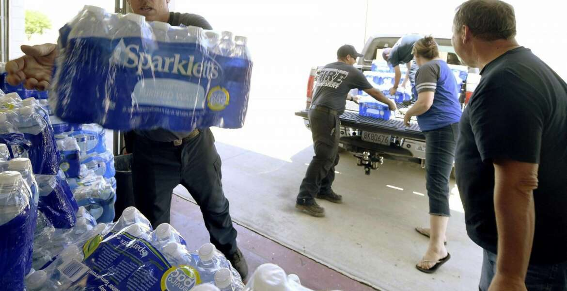 Shawn Dodson, left, with the San Bernardino County Fire Department, stacks cases of water donated by Vince Burns, right, from Ridgecrest, at San Bernardino County Fire Station 57 Saturday, July 6, 2019, in Trona, Calif. The area has been hit with two major earthquakes since Thursday. In Trona, a town of about 2,000 people considered the gateway to Death Valley, fire officials said dozens of structures were damaged. San Bernardino County Supervisor Robert Lovingood said FEMA delivered a tractor-trailer full of bottled water because of damage to water lines. Newsom declared a state of emergency for the county. (Will Lester/The Orange County Register via AP)