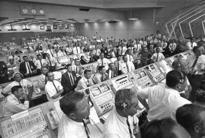 This July 1969 photo provided by NASA shows launch controllers in the firing room at the Kennedy Space Center in Florida during the Apollo 11 mission to the moon. In the third row from foreground at center is JoAnn Morgan, the first female launch controller.