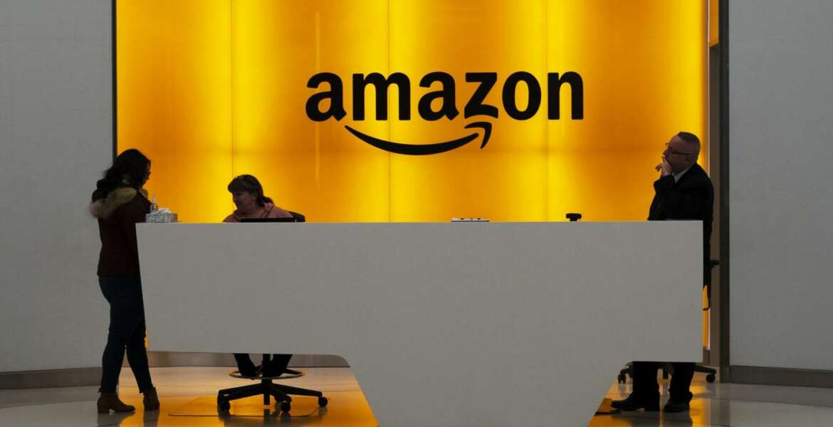 """FILE - In this Feb. 14, 2019, file photo people stand in the lobby for Amazon offices in New York. Amazon and Microsoft are battling for a $10 billion opportunity to build the U.S. military its first """"war cloud."""" (AP Photo/Mark Lennihan, File)"""