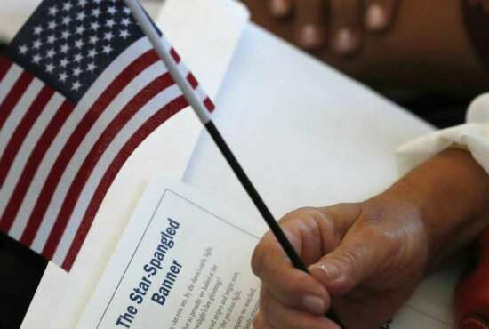 FILE - In this Aug. 16, 2019, file photo a citizen candidate holds an American flag and the words to The Star-Spangled Banner before the start of a naturalization ceremony at the U.S. Citizenship and Immigration Services Miami field office in Miami. U.S. Citizenship and Immigration Services officers can now create fictitious social media accounts to monitor information on foreigners seeking visas, green cards and citizenship.(AP Photo/Wilfredo Lee)