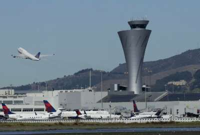 FILE - In this Oct. 24, 2107 file photo, the air traffic control tower is in sight as a plane takes off from San Francisco International Airport in San Francisco. San Francisco International Airport is banning the sale of single-use plastic water bottles. The change will take effect Aug. 20, 2019 and will apply to airport restaurants, cafes and vending machines. (AP Photo/Jeff Chiu, File)