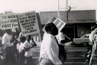 In this 1962 photo, Civil Rights leader Lincoln Ragsdale and supporters march on the Arizona state capitol for the desegregation of public places with the public accommodation bill prior to the Civil Rights Act of 1964. Phoenix's past segregation has been in focus after last month's national outrage over a videotaped encounter of police pointing guns and cursing at a black family.  (Lincoln Ragsdale Jr/Matthew Whitaker Photographs, University Archives, Arizona State University Library via AP)