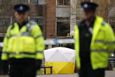 FILE - In this March 6, 2018 file photo, Police officers secure the area as a police tent covers the spot in Salisbury, England, where former Russian spy double agent Sergei Skripal and his daughter, Yulia, were found critically ill following exposure to a nerve agent.  President Donald Trump is levying more sanctions on Russia in connection with the alleged 2018 poisoning of former Russian spy Sergei Skripal and his daughter, Yulia, in Salisbury, England.   (AP Photo/Frank Augstein)