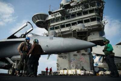 FILE - In this June 3, 2019 file photo, a pilot speaks to a crew member by an F/A-18 fighter jet on the deck of the USS Abraham Lincoln aircraft carrier in the Arabian Sea. The U.S. Navy is trying to put together a new coalition of nations to counter what it sees as a renewed maritime threat from Iran. Meanwhile, Iran finds itself backed into a corner and ready for a possible conflict. It stands poised on Friday, Sept. 6, 2019, to further break the terms of its 2015 nuclear deal with world powers. (AP Photo/Jon Gambrell, File)